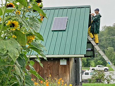 The 100W panel is now charging a battery that is connected to an outlet where the public can plug in to charge their phones, electric saw batteries, blender—whatever you want. We also have a solar powered security light and decorative lights around the shed and picnic area that turn on after dark.